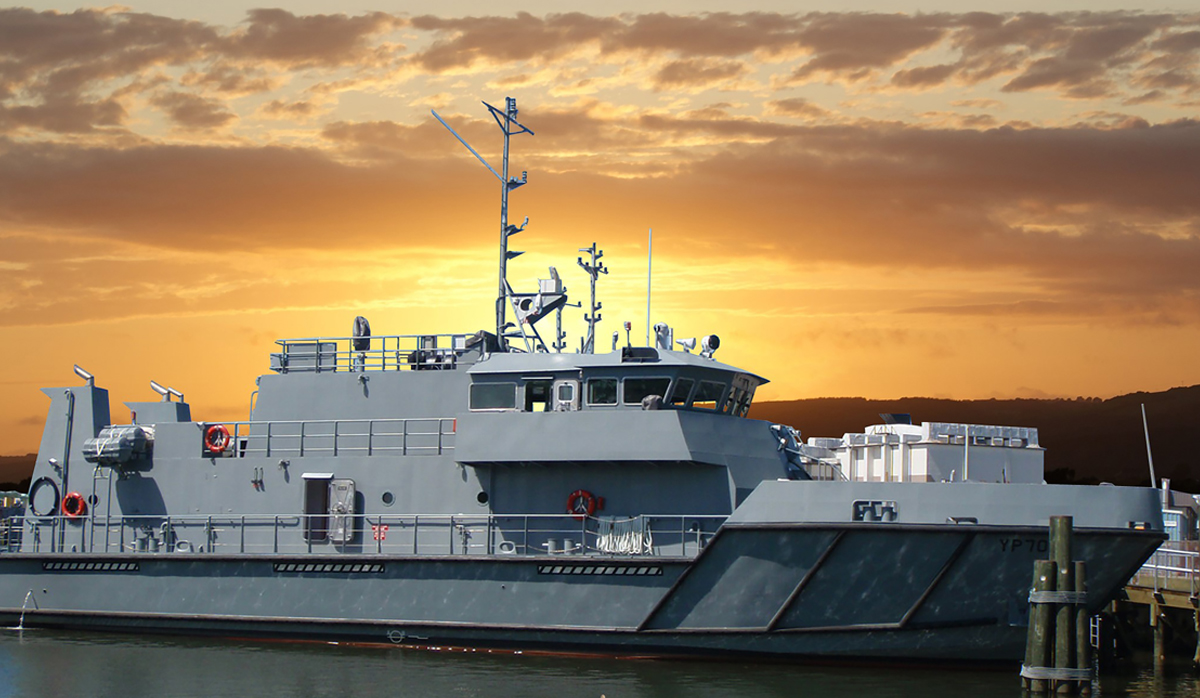Grey ship docked with orange sunset