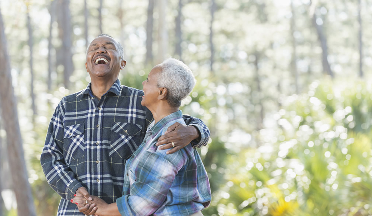 picture of a couple laughing with trees in the background