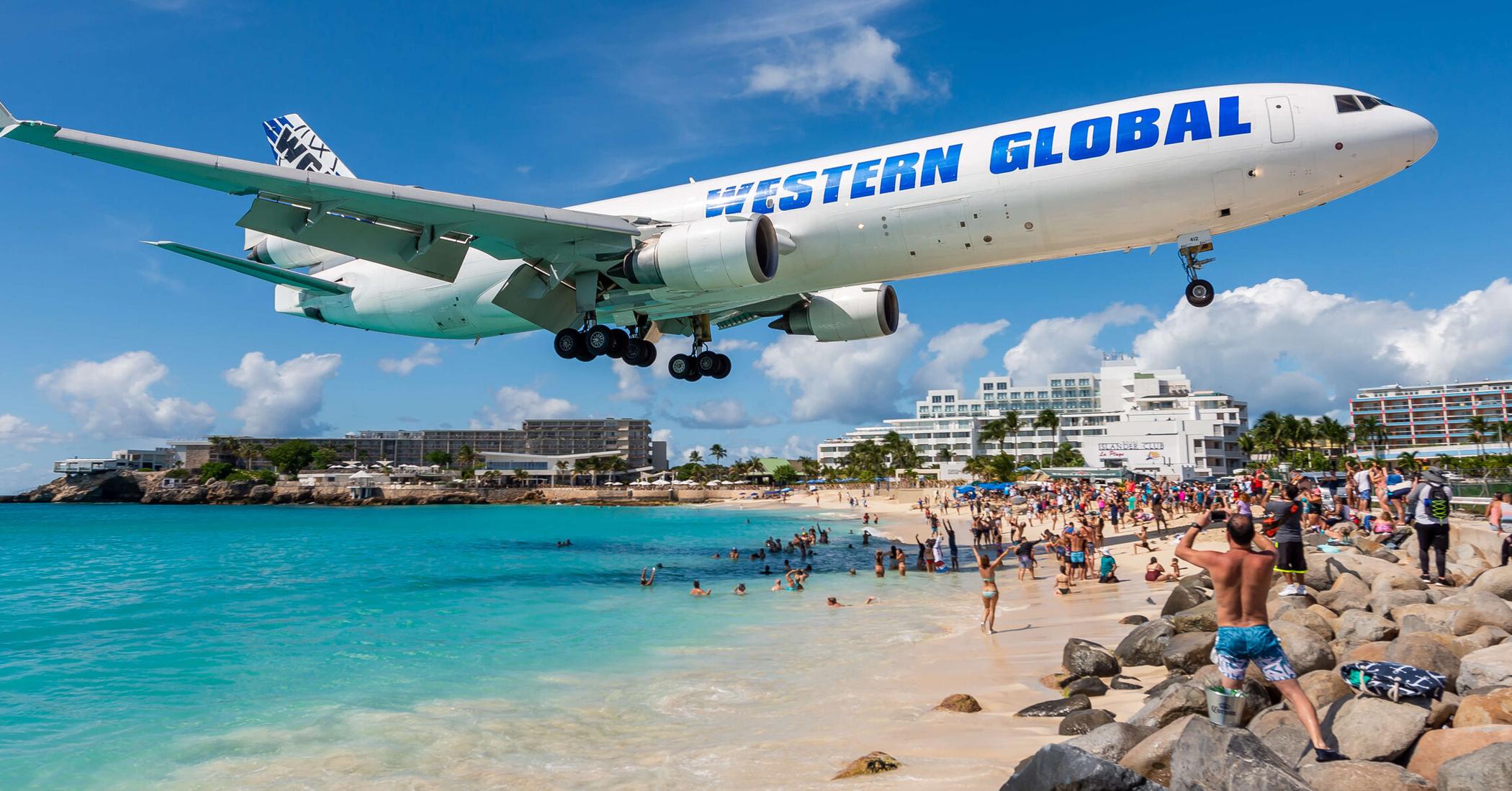Western Global Jet flies over a beach