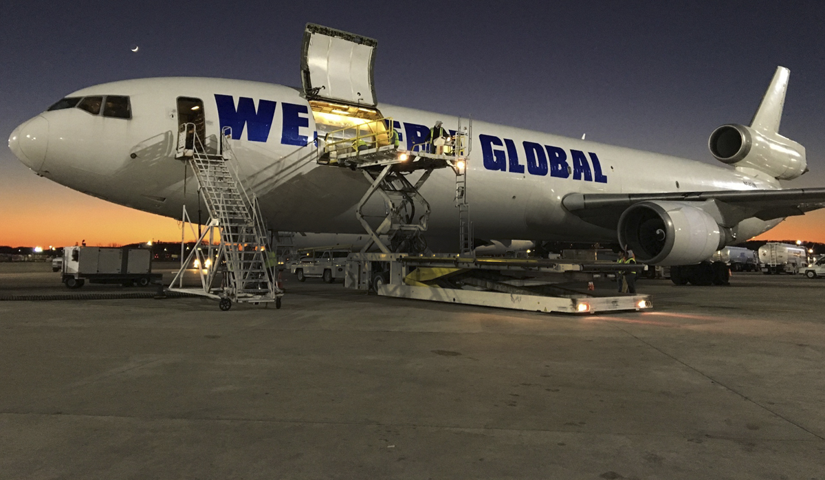 Western Global jet sits on runway with sunset behind it