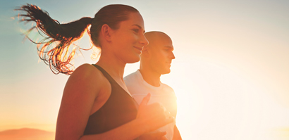 Woman and man running together with sun setting behind them.