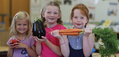 Three kids in classroom holding vegetables and smiling.