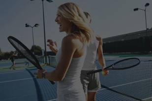 Woman and man on tennis courts holding racquets while laughing.