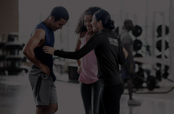 Trainer laughing with two members on fitness floor.