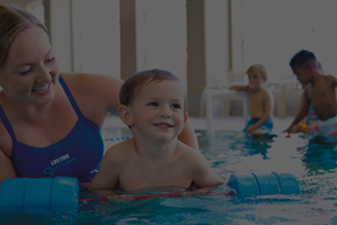 Swim instructor with smiling child in pool.