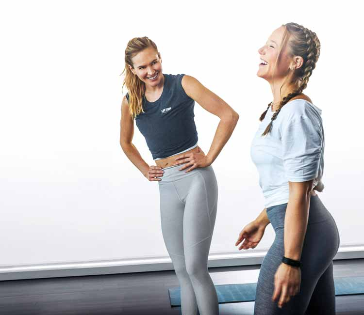 Two women in a studio laughing with a yoga mat behind them.