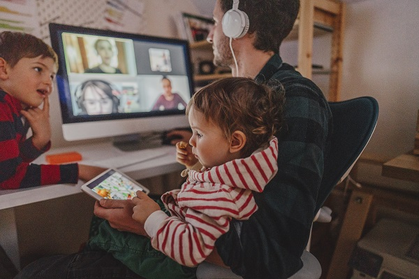father on the computer with two young children