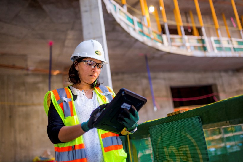 Female student working on a tablet while wearing PPE on a job site