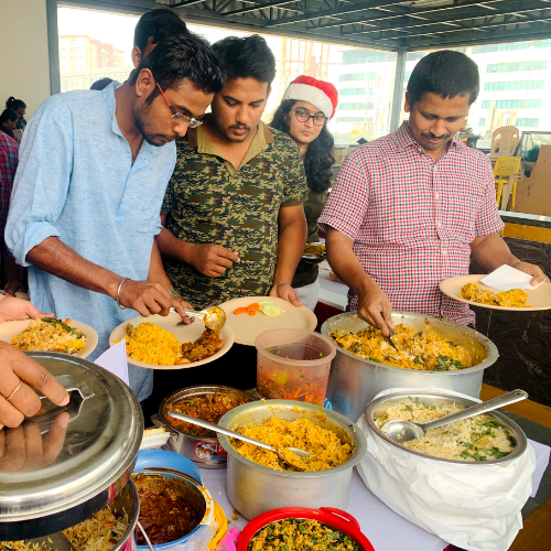 Employees in the India office gather for a pot luck lunch for the holidays