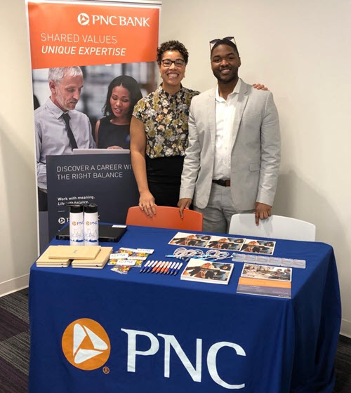two recruiters standing at a PNC booth