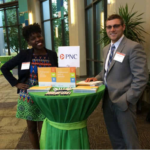 two PNC employees standing together at a table for a picture