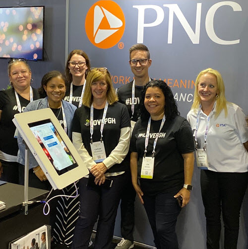 A group of PNC employees standing for a photo at a conference booth