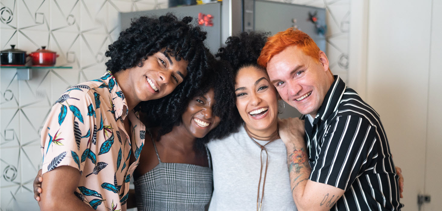 Four people standing close together smiling towards the camera for a group photo.