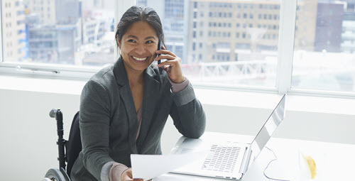 A woman smiling while talking on a cell phone