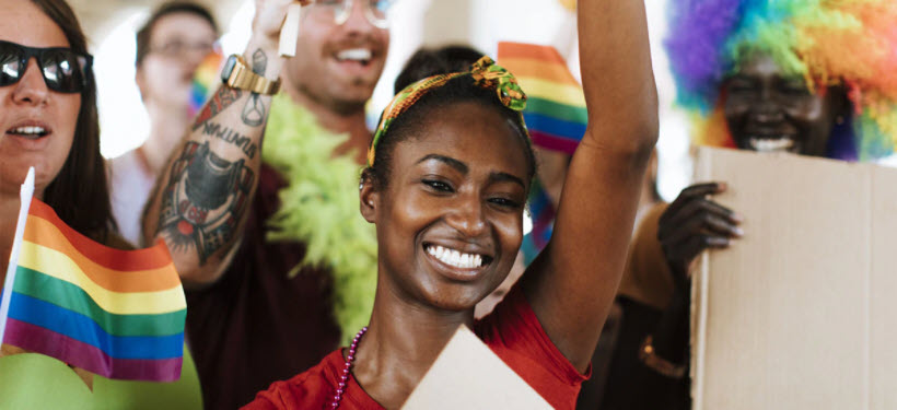 Woman smiling holding a rainbow flag above her head