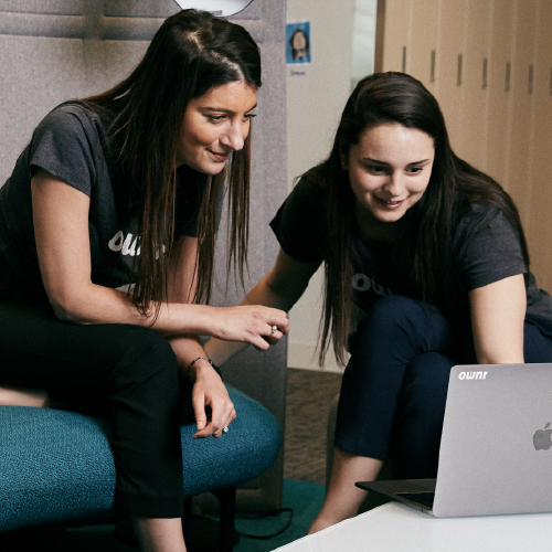 Two female employees conversing and looking at laptop