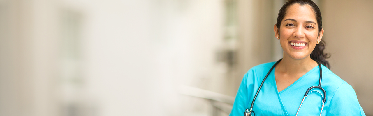 Smiling female healthcare professional looks at the camera while in hospital hallway.