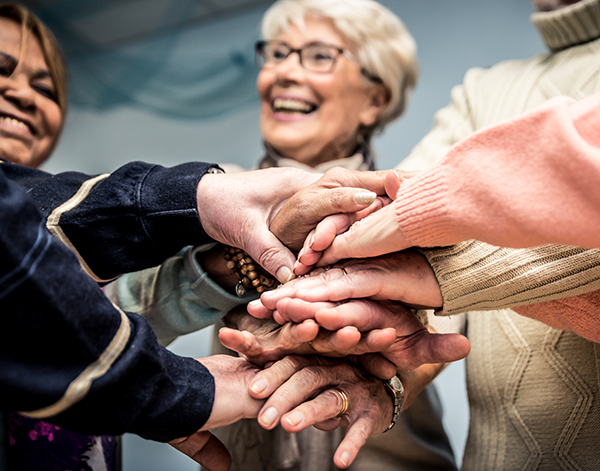 image of a group of seniors put their hands on top of each other to support each other