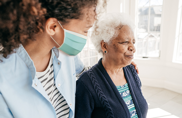 image of a health care aide wearing mask standing beside a female senior
