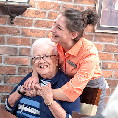 image of a team member hugging a residents and both filled with joy