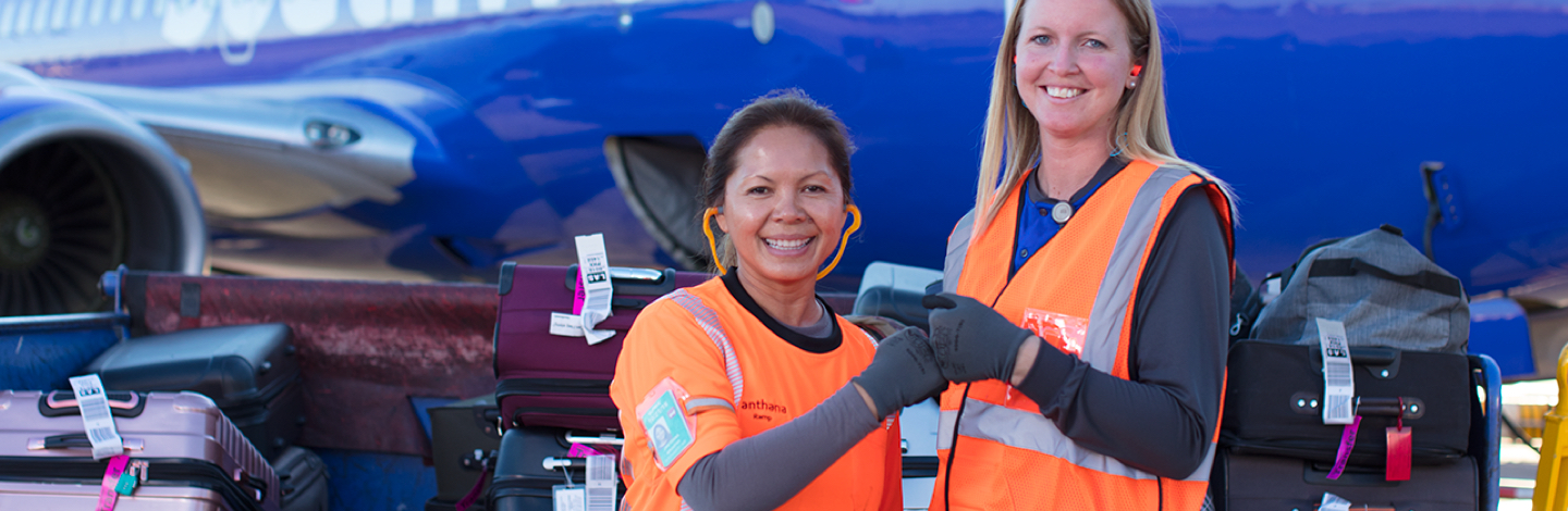 Two female Southwest Ramp Agent Employees fist bumping