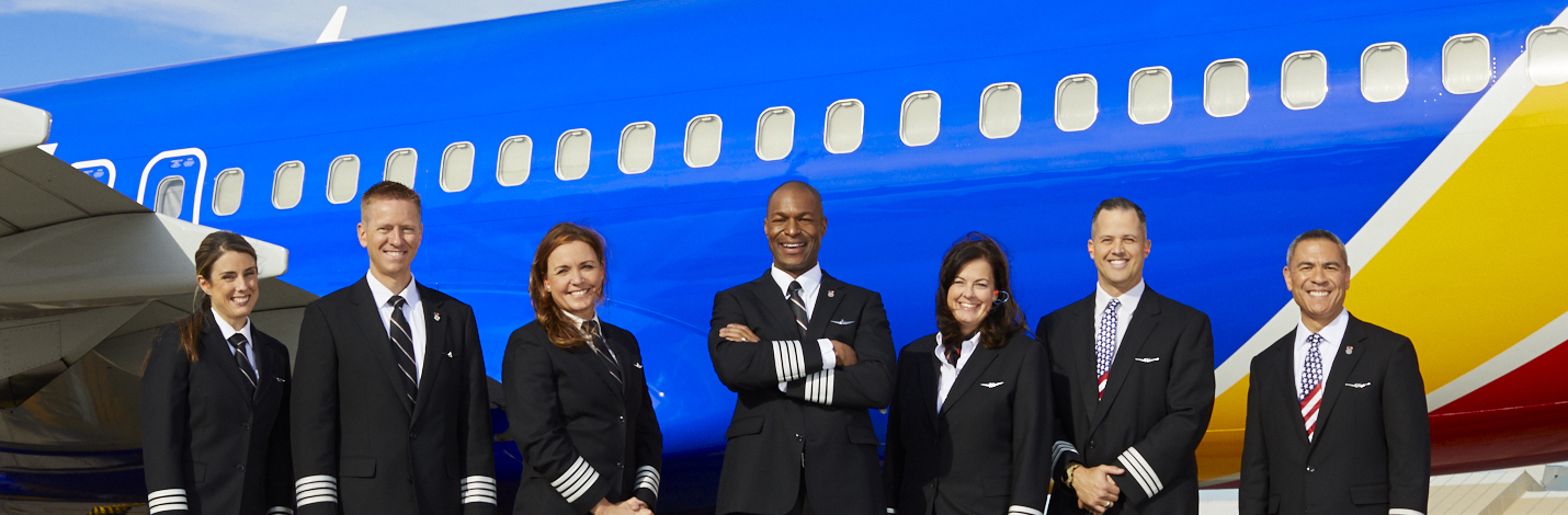 Seven Southwest Pilots stand together next to a plane.
