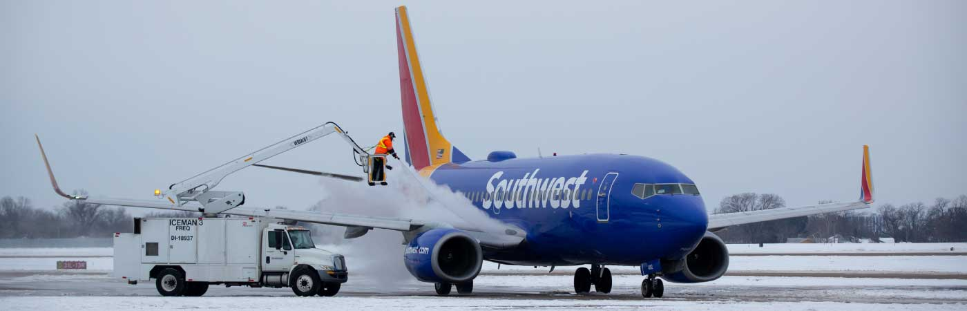 Wide shot of ramp agents deicing a Southwest airplane in the snow from a crane.