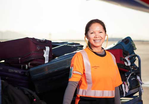 Portrait of female ramp agent smiling and standing in front of a full baggage cart.