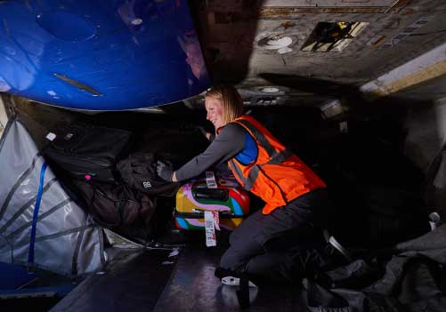 Image of female ramp agent stacking bags inside the belly of an airplane.