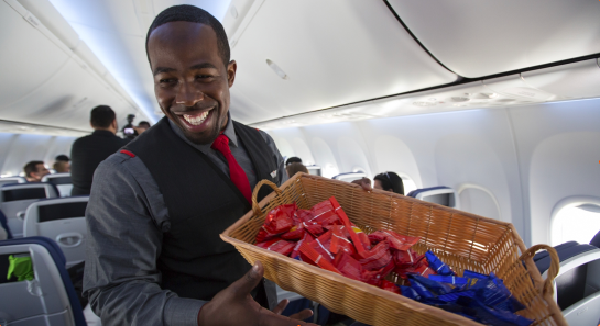 A Flight Attendant passes out pretzels to Customers