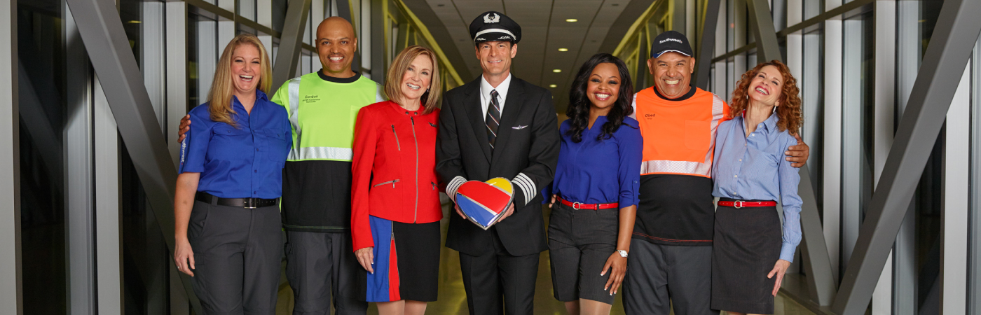 Seven Southwest Employees stand together holding a Southwest Heart