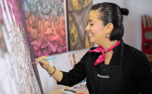 Flight Attendant Wendy Krausbeck paints on a canvas
