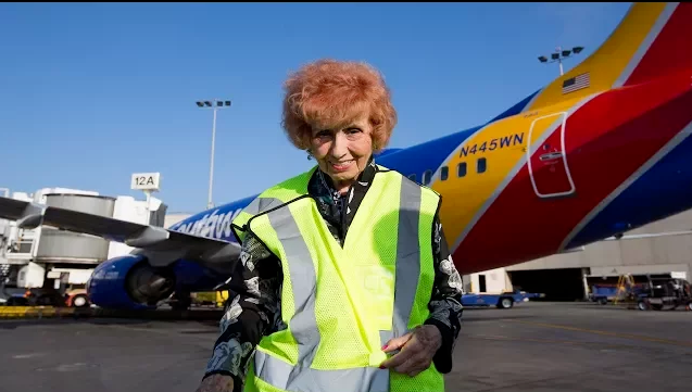 Rosie the Riveter stands in front of an airplane