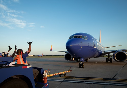Southwest Employees wave at a Southwest plane on the runway