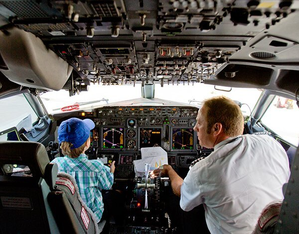 A little boy and Pilot sit in the cockpit of an airplane