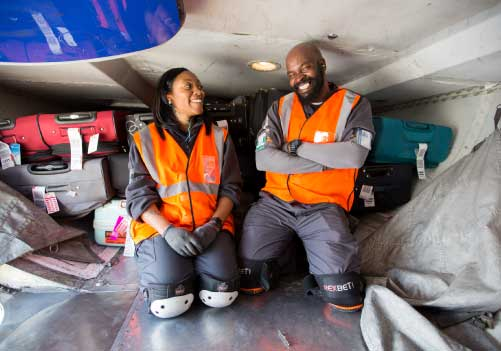 Image of two ramp agents laughing in a cargo bin.