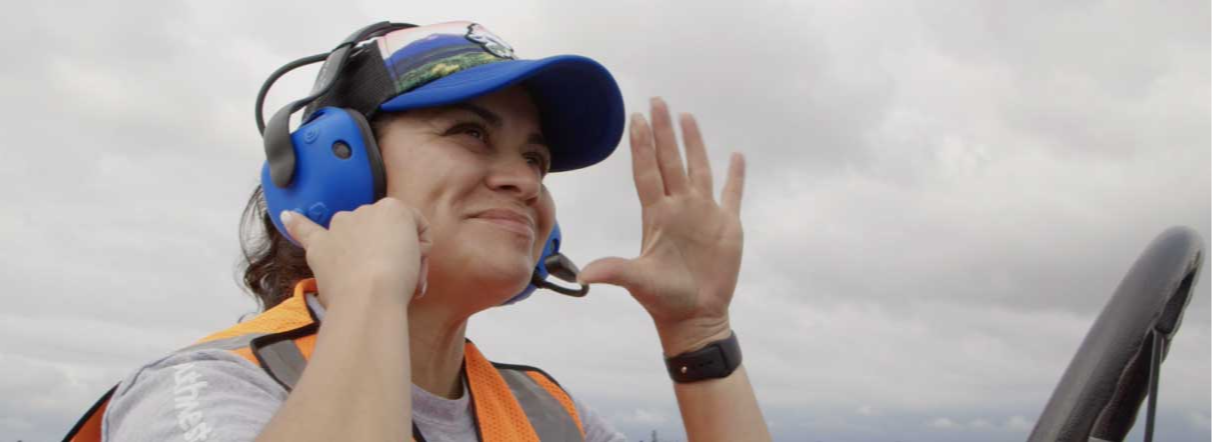 Image of Michelle, a San Diego Ramp agent waving.  She wears a blue hat and a blue headset while sitting in the driver seat of an airplane tug.