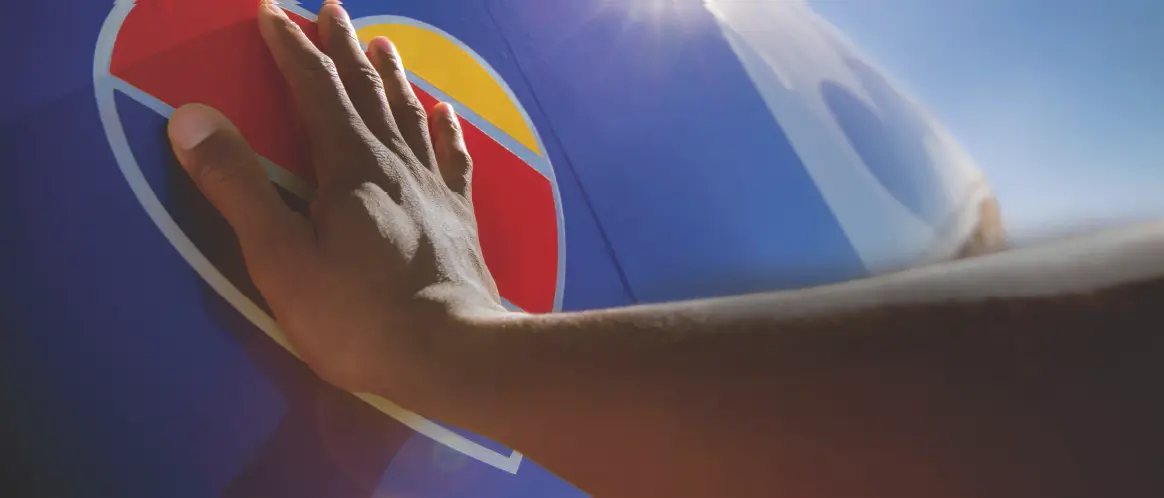 A hand touches the Southwest Heart on a plane