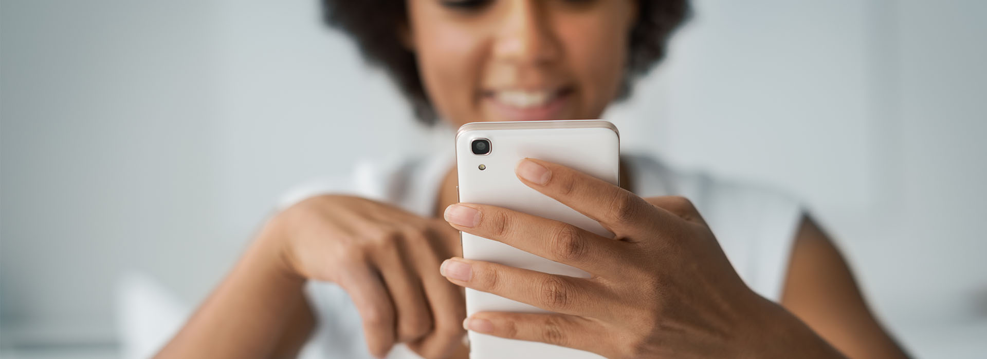 young black woman texting on her mobile phone
