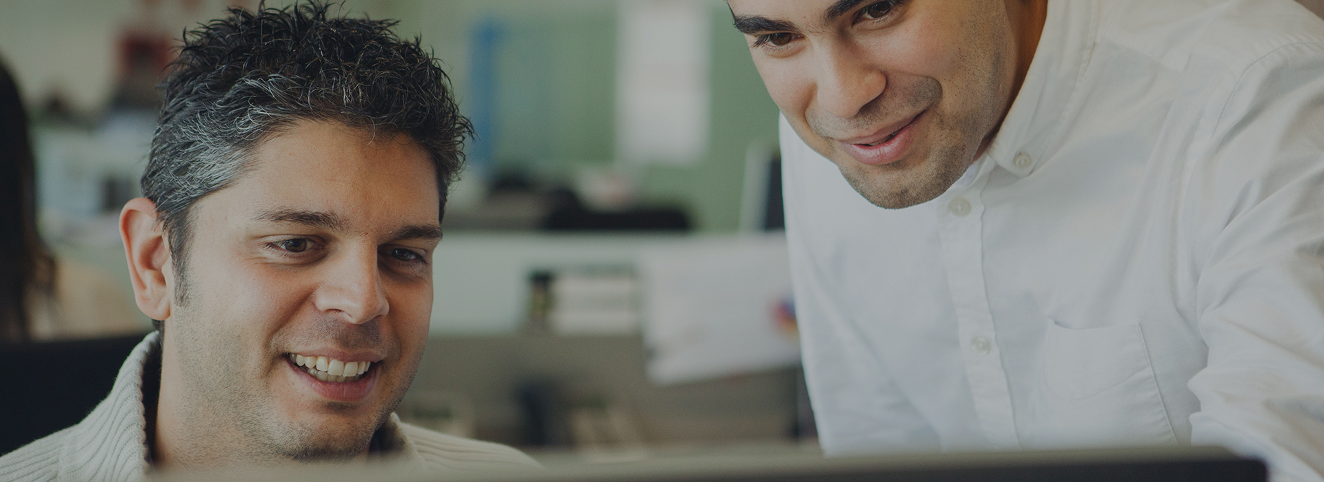2 Unilever employees discussing work on a desktop