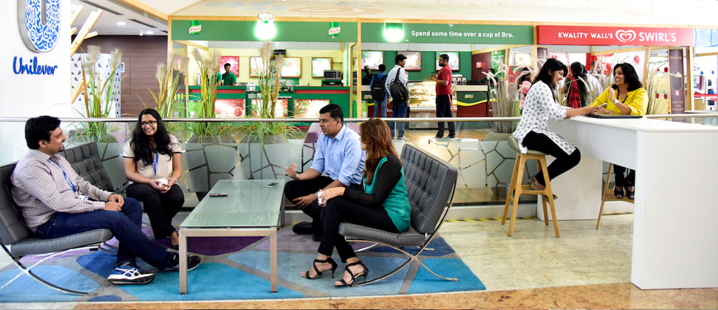 Unilever employees relaxing and chatting in casual office surroundings