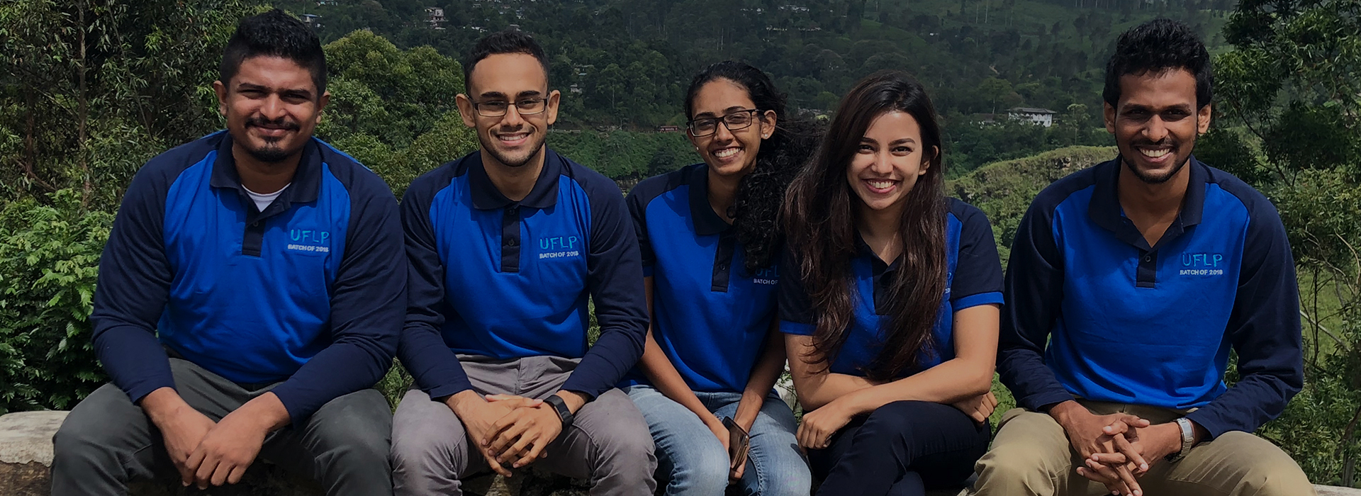 5 smiling people sitting in a row outside in UFLP branded shirts