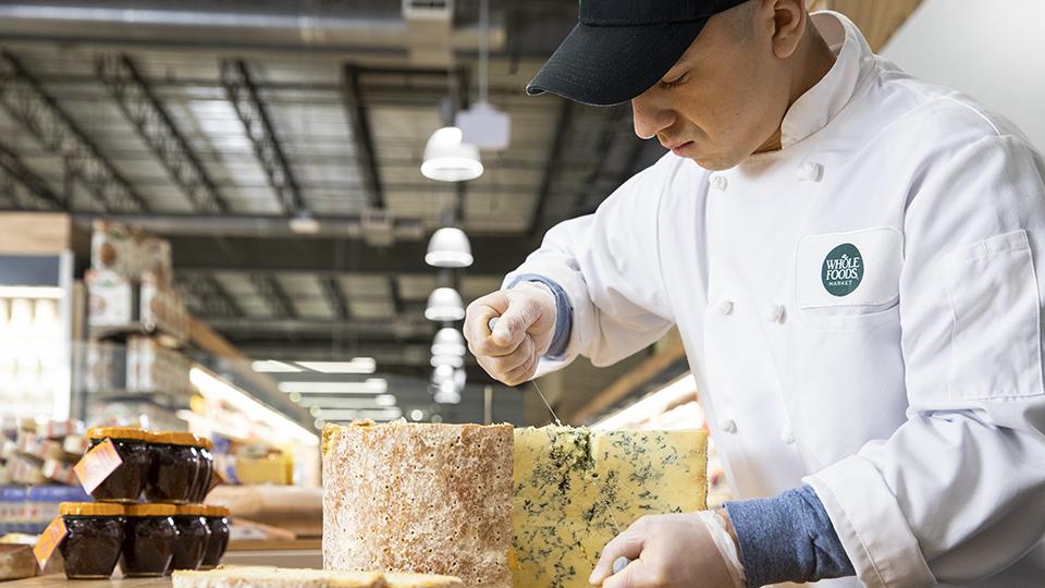 Cheese Team Member Cutting a Block